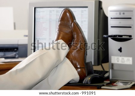An office worker puts his feet up on his desk and ignores the computer work to be done. - stock photo