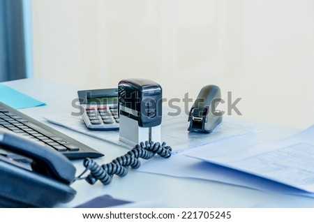 An office workplace with a phone, stapler, documents, stamp; calculator and a computer