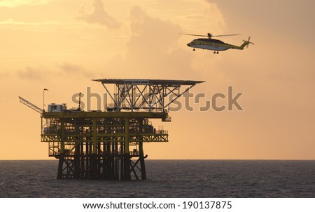 An offshore helicopter for transporting roughnecks approaches a rig - stock photo