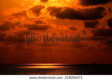 An offshore oil platform at sunrise - stock photo