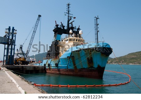 An offshore support vessel anchored on port, sourounded by oil spill barrier. - stock photo