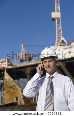 An oil platform inspector on the phone, with the platform in the background - stock photo