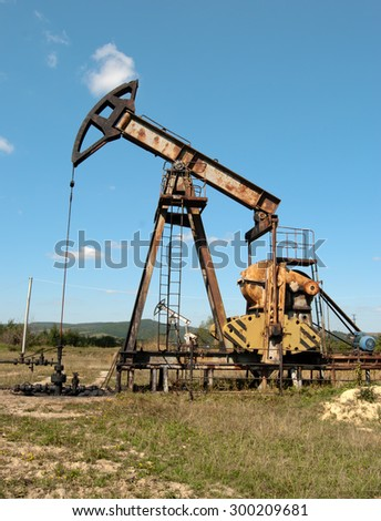 an oil pump is on a background mountains - stock photo