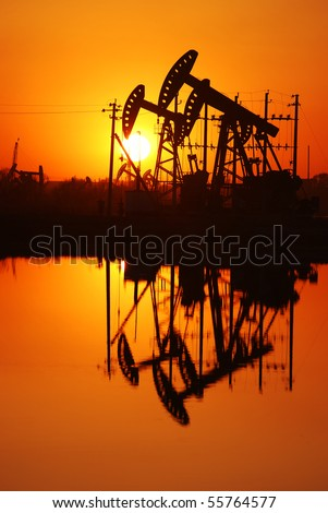 An oil pump jack is silhouetted by the setting sun - stock photo