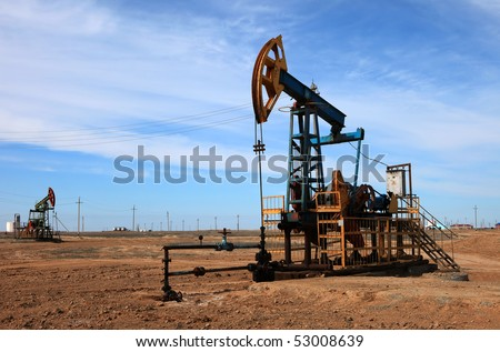 An oil pump jack on blue sky.