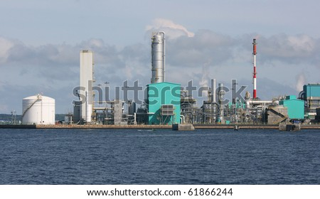An oil refinery on the coast.  This industrial looking building is located near a port.  There is some gas being released, maybe causing some pollution.