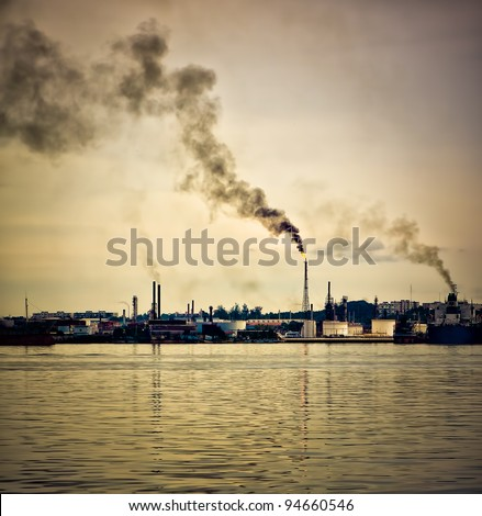 An oil refinery polluting the atmosphere with a huge smoke column pictured at sunset - stock photo