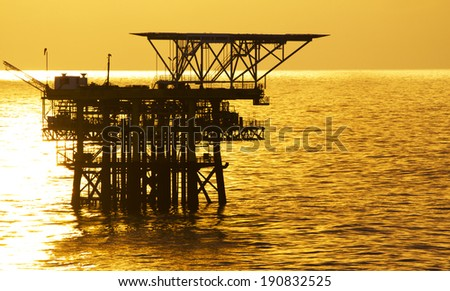An oil rig and a golden sunrise - stock photo
