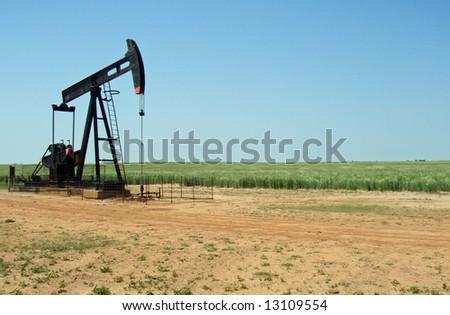 An oil well pump on a rural farm - stock photo