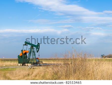 An oil well with the pump jack in action - stock photo