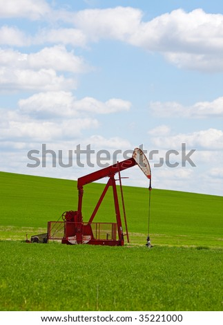An oil well with the pump jack in action, against a grassy, green hill & cloudy blue sky.  Located in the province of Alberta, Canada. - stock photo