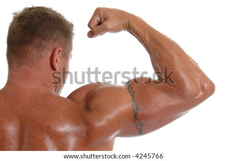 An oiled bodybuilder flexing his bicep for show - stock photo