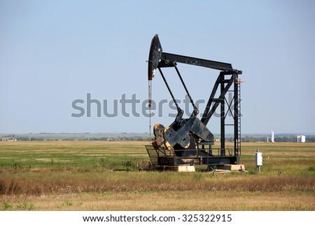 An oilfield pumpjack production on Oklahoma farmland. - stock photo