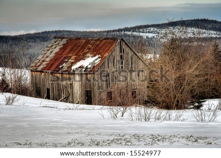 An old abandoned barn in a field at winter - stock photo