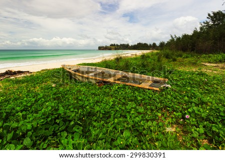An old abandoned boat stranded on a beach - stock photo