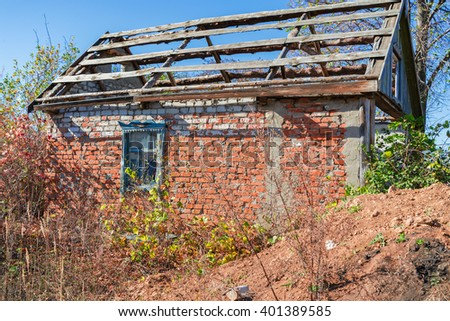 An old abandoned brick house with a broken window, closeup. As background for design of crisis. - stock photo