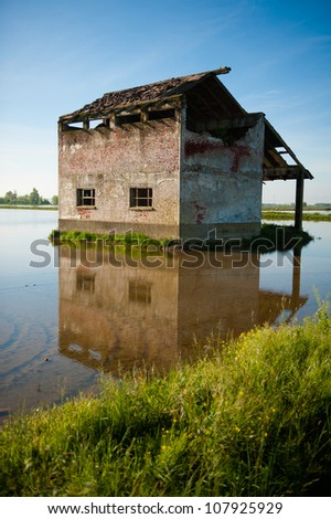 An old abandoned building on a rice field in central Italy - stock photo