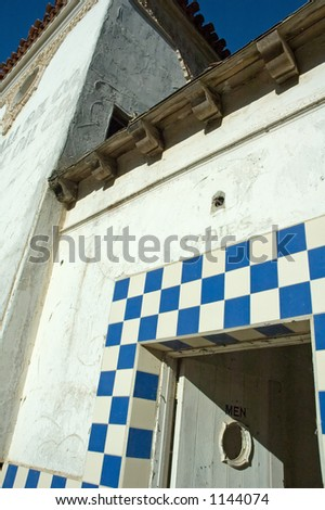 """An old abandoned building showing the open door to the ladies room....with """"men"""" on the door. - stock photo"""