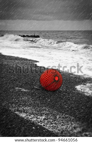 An old abandoned buoy on a beach under a stormy sky - stock photo