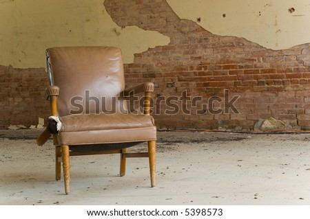 An old abandoned chair left in an abandoned dilapidated building.  Interesting how the colors of the building and the chair match- space for copy