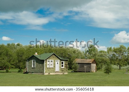 An old abandoned farm house shot on a partly cloudy day with copyspace above - stock photo