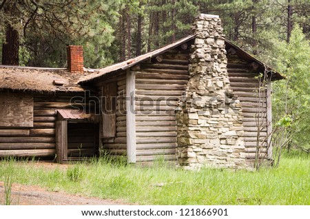 An old abandoned log cabin in the woods - stock photo