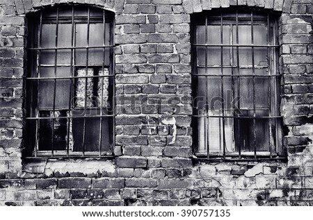 An old abandoned part of the building is a prison. criminal prison cell. brick wall of the prison. dark prison window. prison bars on brick wall. old brick wall background. sinister prison cell. - stock photo