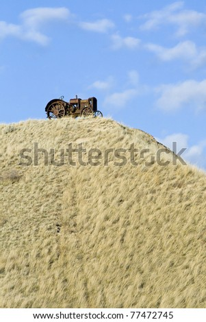 An old abandoned tractor sitting on top of a grassy hill against a cloudy blue sky - stock photo