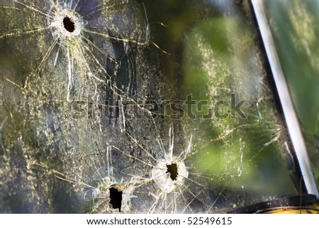 An old abandoned truck in a field with bullet holes in the windshield - stock photo