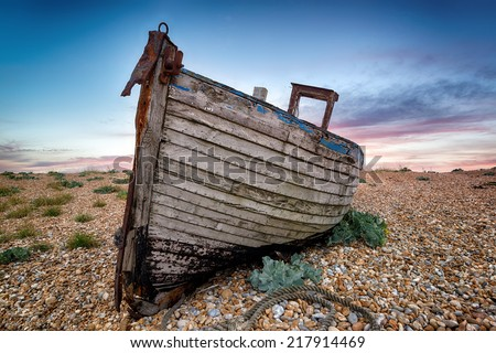 An old abandoned wooden fishing boat high on a shingle beach - stock photo
