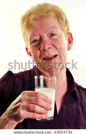 an old age woman is holding a glass of milk