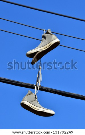 An old all star shoes hanged on electric line. Concept photo of youth, teenage, vandalism ,rebellion,  footwear,  and shoe tossing - stock photo