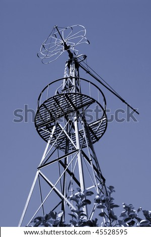 An old and abandoned rusty farm windmill. - stock photo