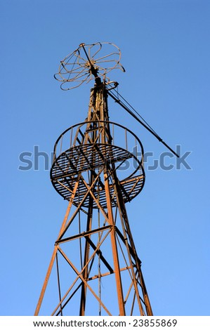 An old and rusty farm windmill. - stock photo
