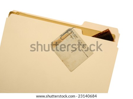 An old and stained post card paper clipped to a manila folder with a few negative strips just inside folder. Isolated on a white background. - stock photo