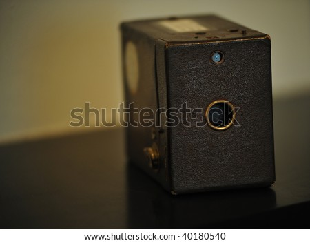 An old antique box camera sitting on a table - stock photo