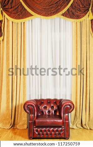 An Old Antique Chair In Front Of The Curtained Window - stock photo