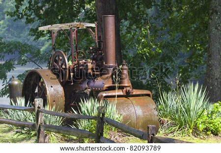 An old antique steam roller is parked in a grassy field
