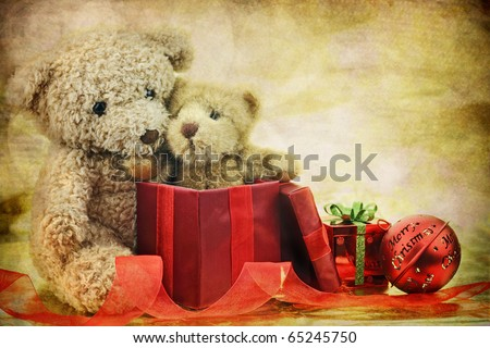 An old antique teddy bear hugs his Christmas gift, a new little teddy bear friend, while surrounded by ornaments and ribbons . Copy space available. - stock photo