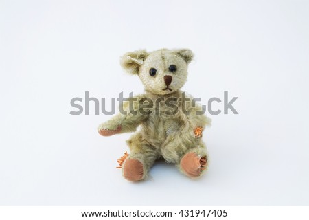 An old, antique teddy bear with holes and his stuffing coming out. A simple white, horizontal background. Cute and adorable for a variety of ideas and concepts. - stock photo