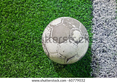 an old ball with white line on green field - stock photo