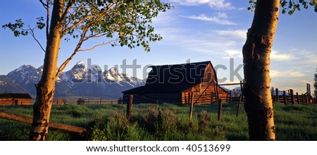An old barn, corral and aspen trees, with the Grand Teton Mountain Range in the background. - stock photo