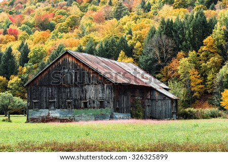 An old barn in a Vermont field during New England's Fall Foliage season - stock photo
