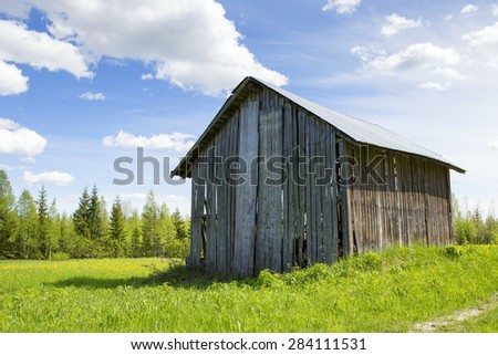An old barn in the countryside. Image taken in a sunny day in Finland. - stock photo
