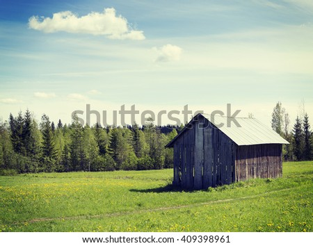 An old barn in the countryside. Image taken in a sunny day in Finland. Image has a vintage effect applied. - stock photo