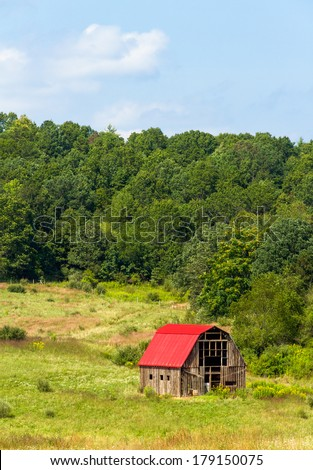An old barn with a bright red roof punctuates farmland in the hills of western Virginia. - stock photo