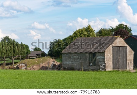 An old barn with wooden doors in a Dutch landscape.  Green grass in the foreground. The sky is blue with white clouds. Some green trees in the background.