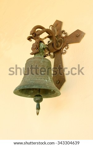 An old bell at the wall of a church. - stock photo