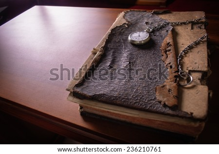 An old Bible with pocket watch on the table - stock photo