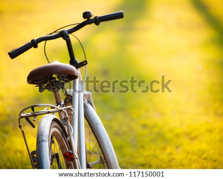 An old bicycle in meadow during sunset with shallow dept of field - stock photo